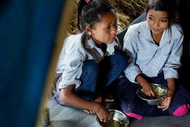 Dos niñas nepalíes comiendo en el interior de una tienda