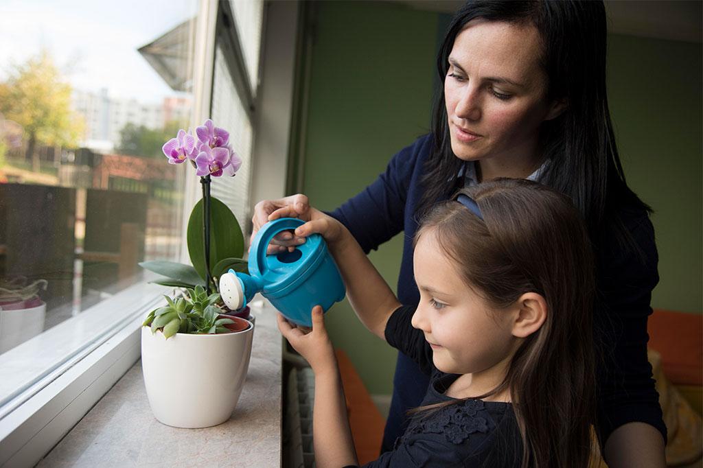 Mujer y niña regando una planta