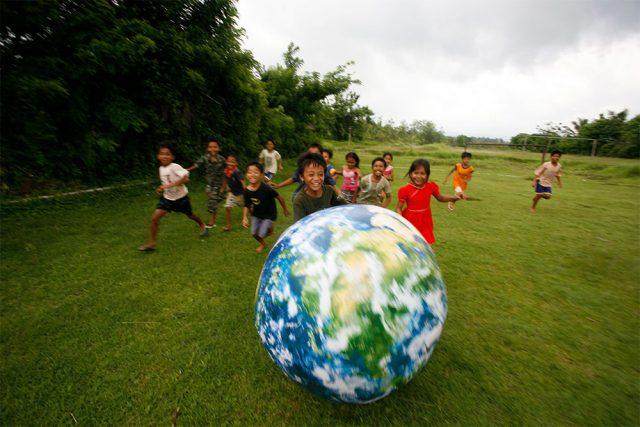 Niños corriendo detrás de una pelota del mundo