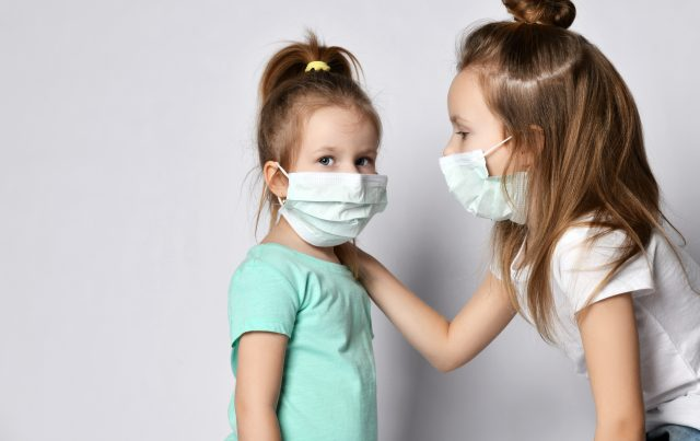 Two children girls kids are afraid of the disease in protection masks from the Coronavirus Covid-19